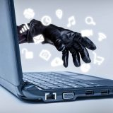 A gloved hand reaching out through a laptop with common media icons flowing, signifying a cybercrime or Internet theft while using various Internet media.