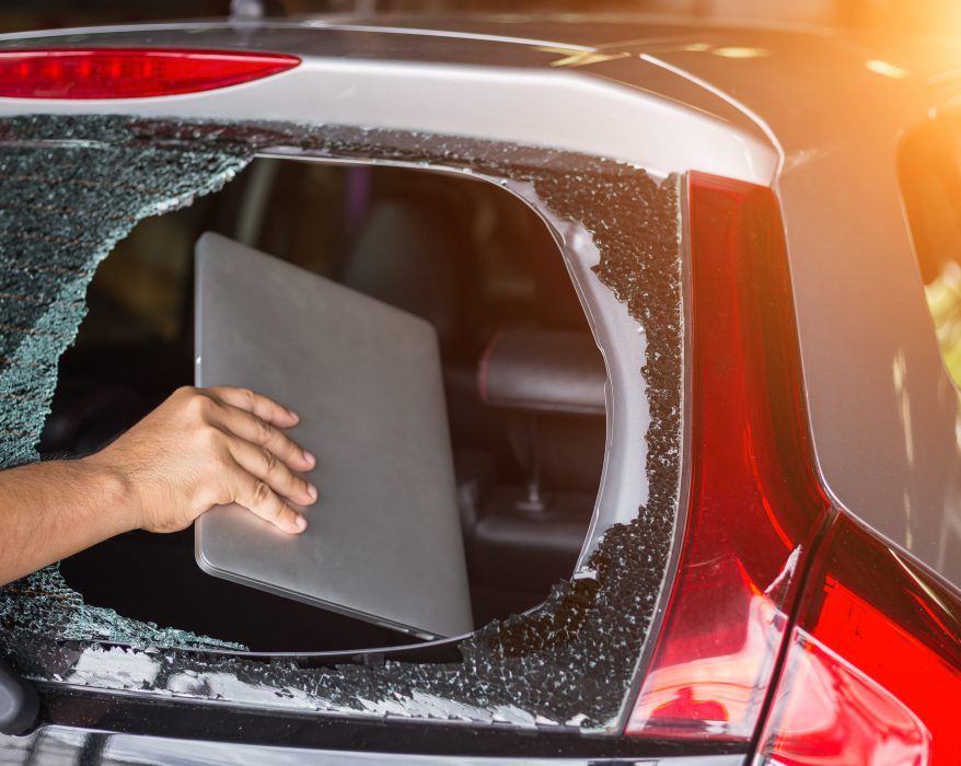 Hand stealing laptop from back side of car which rear glass broken