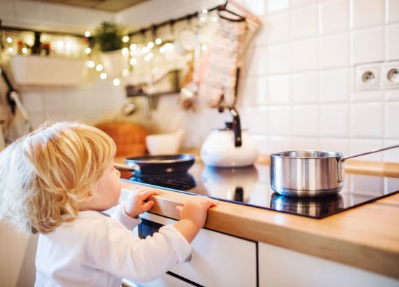 Kid-in-the-kitchen-checking-over-the-kitchen-stove