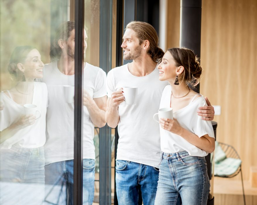 Young-and-happy-couple-homeowners-dressed-in-white-shirts-standing-together-with-cups-near-the-window-at-home
