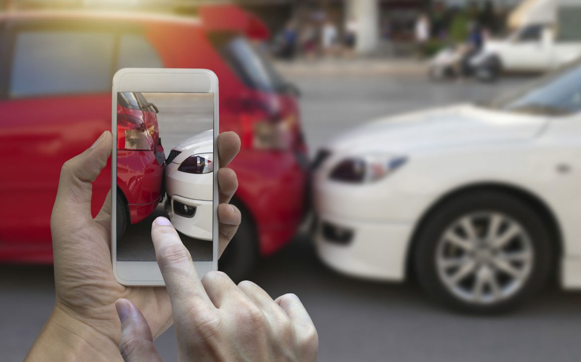 hands-holding-a-mobile-phone-and-taking-a-photo-of-a-car-accident-1