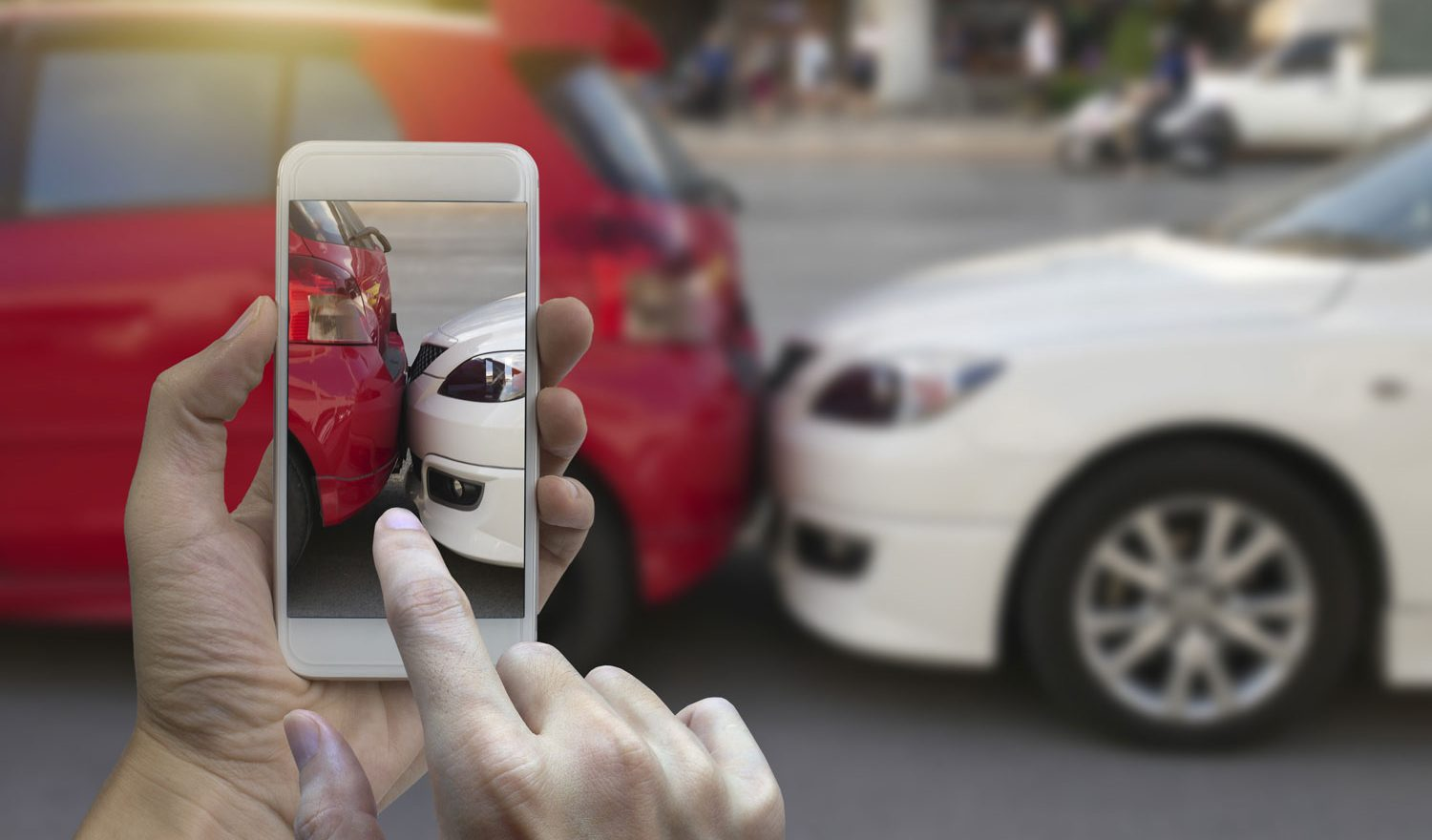 hands-holding-a-mobile-phone-and-taking-a-photo-of-a-car-accident