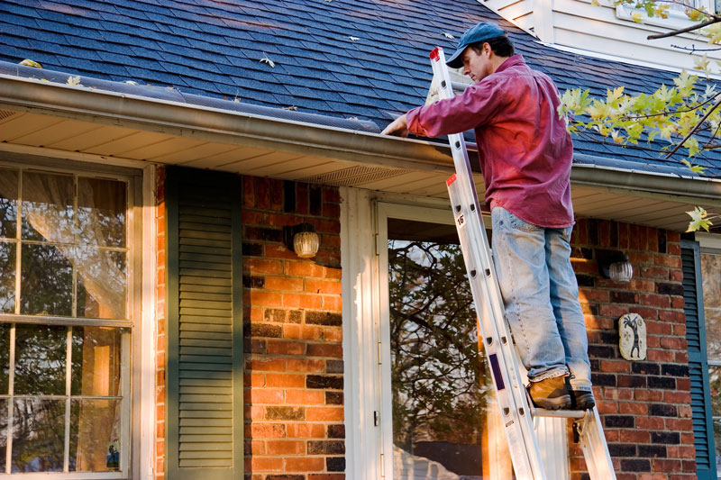 man-inspecting-and-fixing-roof-of-house